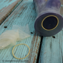 Photo shows a discarded condom with the base ring torn off laying next to a large purple silicone dildo that has been covered entirely in a condom, from tip to base